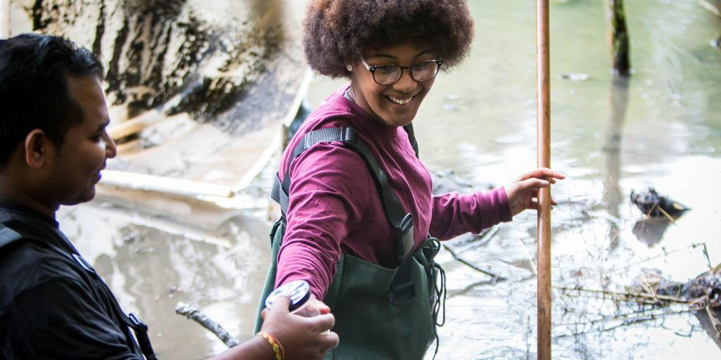 Biological Studies student conducting research in stream
